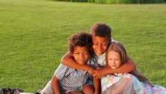 Three beautiful children are playing on the sunny glade Stock Footage