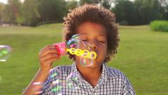 Cute boy is making bubbles on the sunny glade closup. Stock Footage