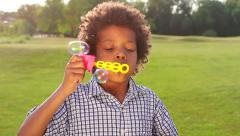 Stock Video Footage of Fun boy is making bubbles on the sunny glade closup.