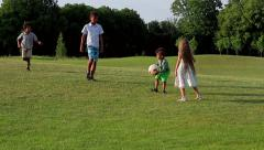 Kids are playing with a ball on evening glade. Stock Footage