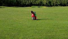 Cute afro boy plays and drives with the red motorbike toy on the sunny glade. Stock Footage