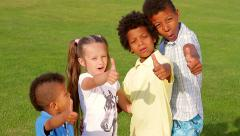 Happy children are playing in a garden and showing big finger up. - stock footage