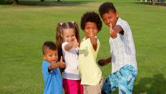 Four happy children are playing in a garden and showing big finger up. Stock Footage