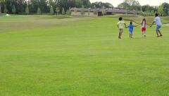 Stock Video Footage of Four children are playing on the glade. They are jumping and laughing.