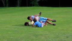 Stock Video Footage of Children are lying on the sunny glade, laughing and fighting.
