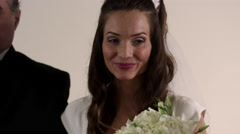 Close-up of a bride looking hesitant as she is escorted down the aisle. - stock footage
