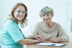 Kind female medic with patient - stock photo