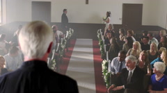 Father walking bride to the preacher at the front of a chapel. Stock Footage