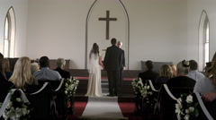 Looking up a church aisle at a bride, groom, and preacher. Stock Footage