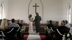 Preacher talking to a bride and groom in a chapel. Stock Footage