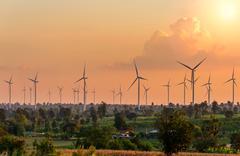 Eco power in wind turbine farm with sunset - stock photo