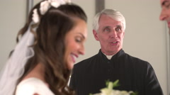 Bride and groom facing each other as the preacher talks to them. Stock Footage