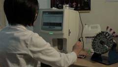 Medical technician analyzing blood with modern digital equipment, close up. Arkistovideo