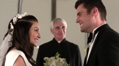 Bride and groom kiss and smile at the front of the chapel. - stock footage