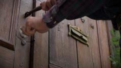 Low angle of a man opening an antique wooden door Stock Footage