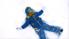 Happy child playing in the snow angel Stock Footage