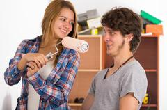 Couple renovating together as she holds up a roller with pink paint in front of Stock Photos