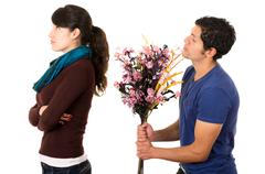 Hispanic couple fighting as man attempts to give girlfriend flowers but she Stock Photos