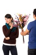 Man tries to give girlfriend flowers but she dimsisses him by holding up her Stock Photos