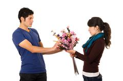 Hispanic man hesitantly receives flowers from shameful looking girlfriend Stock Photos