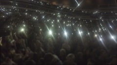 Stadium full of people waving hands, phone screens shine in darkness, love song Stock Footage