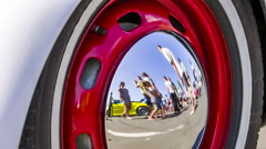 People Reflected In the Hubcap Of Old Car Wheel Disk - stock footage