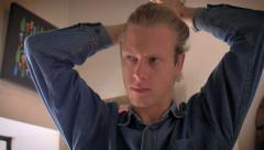 An attractive young long hair blond man puts hair in a man bun Stock Footage