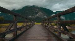 An old beautiful footbridge over a mountain lake Stock Footage