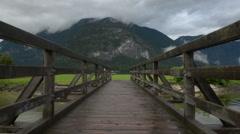 An old beautiful footbridge over a mountain lake. Stock Footage