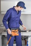 The plumber in the kitchen - stock photo