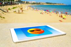icon of a sun sweating in a tablet computer at the beach - stock photo
