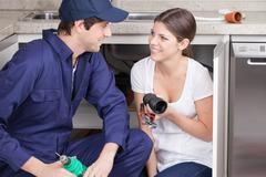 Pair of plumbers with plumbing parts Stock Photos