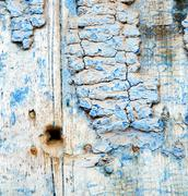 Stock Photo of metal nail dirty stripped paint in the brown wood door and rusty  yellow