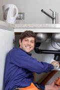 Happy plumber placing a pipe Stock Photos