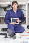 Serious plumber with his tablet Stock Photos