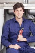 Young plumber holding his wrench - stock photo