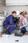 Woman supervising plumber Stock Photos