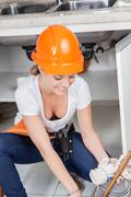 Plumber working in the kitchen - stock photo