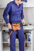 Plumber in the kitchen Stock Photos