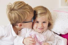 Boy kissing little sister's cheek Stock Photos