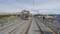 Yellow train on Dom Luis bridge in Porto Stock Footage