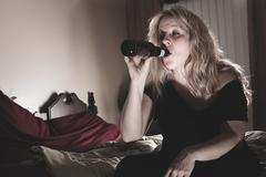 A alcoholic woman drinking beer in his bedroom Stock Photos