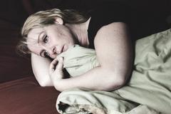 A woman inside is bedroom feel depress - stock photo