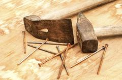 Old used hammer, adze and rusty nails - stock photo