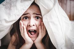 white Caucasian young teenage girl hides under his blankets and covers - stock photo
