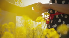 Couple holding hands in rape oil field Stock Footage
