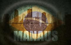 sniper scope aimed at the abstract silhouette of the city with text Manaus at - stock illustration