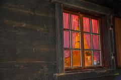 Homely vibe behind the window with glazing bars of a log cabin Stock Photos