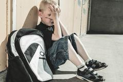 Stock Photo of A very sad boy in school playground
