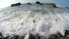 Slow motion of splashing waves on a wild pebble beach Stock Footage